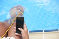 Searching for summer music. Woman searching music track in her smartphone when resting by swimming pool royalty free stock photos
