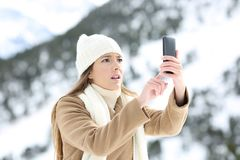 Woman searching phone coverage in winter. Desperate woman searching mobile phone coverage in winter holidays in a snowy mountain Royalty Free Stock Photo