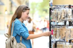 Woman searching products in a showcase. Side view portrait of a happy woman searching products in a showcase in the street Stock Photography