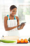 Woman searching recipe. Beautiful young afro american woman searching for a recipe using tablet computer Royalty Free Stock Photos