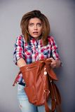 Woman searching something in bag. Confused woman searching something in her bag over gray background and looking at camera stock photo