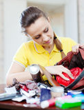 Woman searching something in handbag. Inconsiderate woman searching something in handbag at home Royalty Free Stock Images