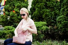 Young blond woman searching for stuff in her handbag stock image