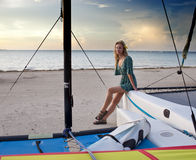 Woman on the seashore sits on board a catamaran Stock Photography