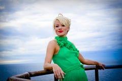 Woman at seaside. A portrait of a beautiful blond woman posing near a railing on seaside Royalty Free Stock Photo