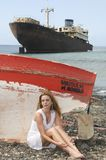 Woman in the seaside near an abandoned ship Stock Photo