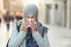 Woman with a seasonal winter cold blowing her nose. On a handkerchief or tissue as she walks down an urban street in a health and medical concept stock photo