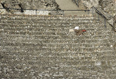 Woman seated alone at the Amphitheater of the Three Gauls in Lyon, France stock photos