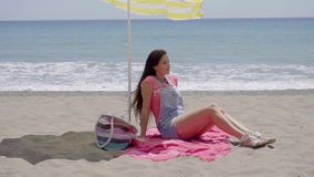 Woman seated on blanket at beach. Cute thoughtful young woman in pink with long brown hair seated in shade at sandy ocean beach with hand under chin stock video footage