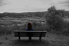 Woman seated contemplating a country landscape Stock Photo