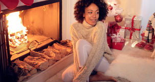 Woman seated by fireplace and holiday setting Stock Photos