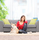 Woman seated on the floor at home, with her dog. Young woman relaxing at home seated on the floor with her pet dog in front of a modern sofa shot with tilt and Stock Photo