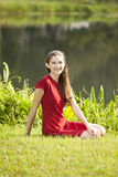 Woman seated on grass stock images