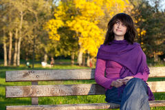 Woman seated on park bench Royalty Free Stock Photos