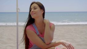 Woman seated in shade at beach with hand on neck. Gorgeous young beautiful woman with long black hair seated in shade at sandy ocean beach with hand on neck stock footage