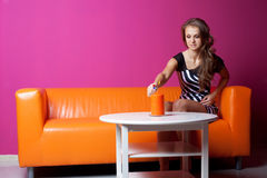 Woman seated on a sofa Stock Photos