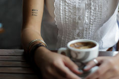 Woman seated at table holding coffee cup Stock Photo