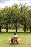 Woman seated at a table, relaxing in a park in the centre of Edinburgh Royalty Free Stock Photo
