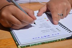 Woman seated at a table, writing in a bullet journal stock images