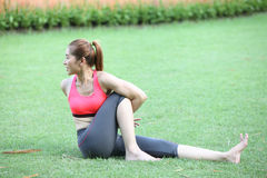Woman in Seated Twist Yoga Pose on lawn Royalty Free Stock Photos