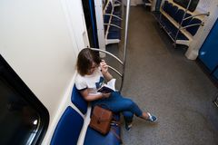 Girl seats in empty subway train. She is in blue jeans and white t-short stock photos