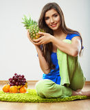 Woman seating on floor with fruits. Royalty Free Stock Image