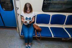 Girl seats in empty subway train. She is in blue jeans and white t-short stock photo