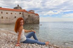 Woman is seating on sea coast. Montenegro Royalty Free Stock Photography