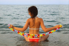 Woman seats in the water on sea Stock Image