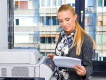 Woman secretary with copy machine Royalty Free Stock Images