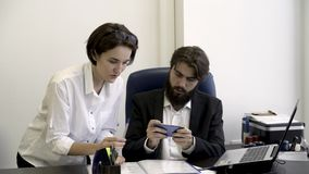 Woman secretary shows important documents to her bearded boss who is busy with playing smart phone games in the office stock video
