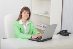 Woman - secretary sits on workplace with compute Royalty Free Stock Photography