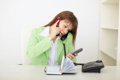 Woman - secretary speaks by several phones Stock Photography