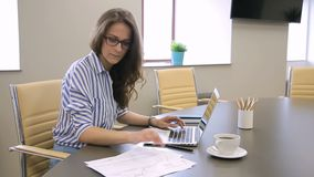 Woman secretary works, using laptop and documents sitting at table in company. Female in glasses looks at papers carefully and types text, tapping with fingers stock video