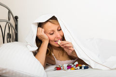 Woman secretly eating candy in bed Royalty Free Stock Photos
