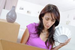 Woman securing fragile objects in box before moving. Woman securing her fragile objects in the box before moving Stock Photos