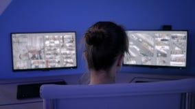 Woman security guard looking at modern cctv camera monitors
