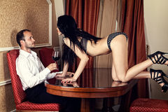 Woman seduces a man with a glass of wine Royalty Free Stock Image