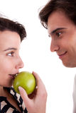 Woman seducing a man eating an apple Royalty Free Stock Photography