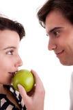 Woman seducing a man eating an apple Royalty Free Stock Photography