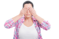 Woman in the see no evil pose. While covering her eyes isolated on white Royalty Free Stock Image