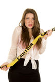 Woman see through shirt red bra danger scared. A woman with a scared expression on her face, holding on to caution tape stock photos