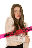 Woman see through shirt red bra danger serious. A woman in her sheer top with a red bra, with danger tape across her Royalty Free Stock Image