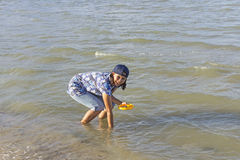 Woman seeking shells in the shallow water during low tide Stock Photo