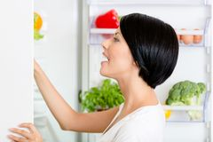 Woman seeks food in the opened fridge. Full of vegetables and fruit. Concept of healthy and dieting food royalty free stock photo