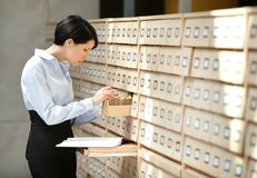Woman seeks something in card catalog. Composed of set of wood boxes at the library. Knowledge Royalty Free Stock Image