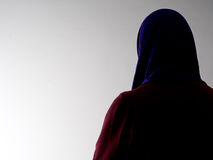 Woman seen from behind,disguised. Violence against women etc. Woman seen from behind,disguised. Violence against woman etc. Scarf covering hair for anonymity royalty free stock images