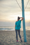 Woman seen from behind in fitness gear watching sunset on beach Stock Images