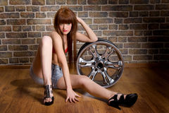 Woman seet with wheel in garage Stock Photography