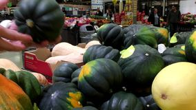 Woman selecting acorn squash in grocery store
